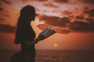 girl is reading a book in the sunset